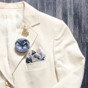 cream blazer with grey lapel flower and black and tan pocket square inside pocket