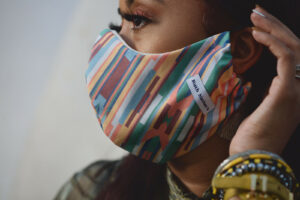 Side view of woman wearing multi color bias stripe face mask