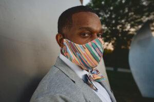 Side view of man wearing multi color bias stripe face mask