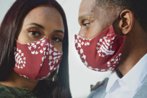 Couple wearing matching crimson and cream curved face masks