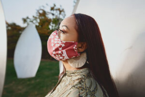 Side view of woman wearing crimson and cream curved face mask