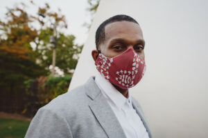 Man wearing crimson and cream curved face mask