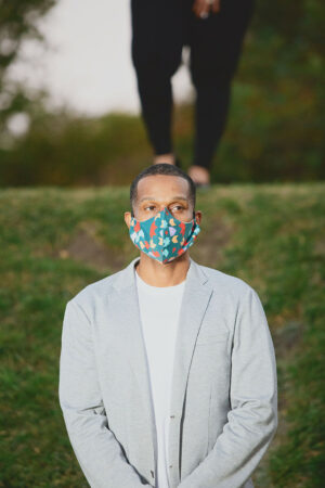 Man wearing evergreen curved face mask with red, teal and purple print