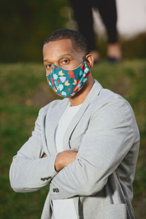 profile of Man wearing evergreen curved face mask with red, teal and purple print