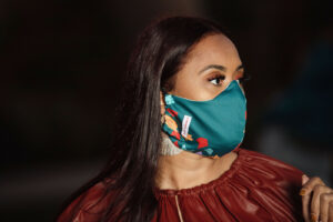 profile of woman wearing evergreen curved face mask with red, teal and purple print