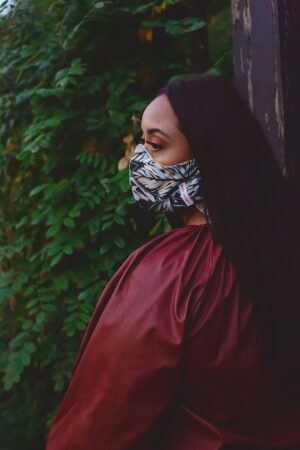 profile of woman wearing black cotton mask with grey, tan and white botanical print