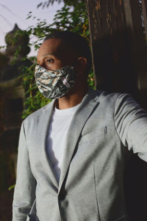 profile of man wearing black cotton mask with grey, tan and white botanical print