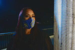 profile of woman wearing blue curved mask with yellow tile accents
