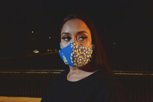 woman wearing blue curved mask with yellow tile accents