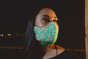 profile of woman wearing Green curved face mask with Pink tile accents
