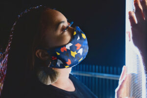 Woman wearing Navy face mask with blue, yellow and red geometric print
