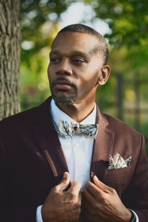 Man wearing black skinny bow tie with botanical print and matching pocket square