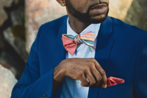man adjusting pink pocket square with matching bow tie