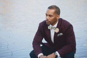 Man wears cream flower pin and black botanical print pocket square