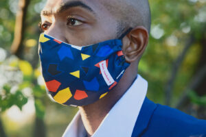 Man wearing Navy face mask with blue, yellow and red geometric print