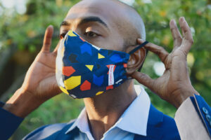 Man putting on Navy face mask with blue, yellow and red geometric print