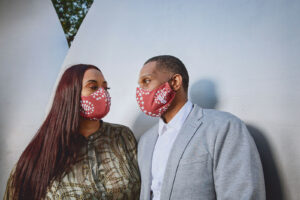 Couple wearing matching crimson & cream curved face masks